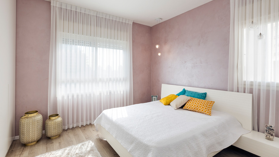 חדר שינה המכיל צבעי קיר שונים למראה נקי