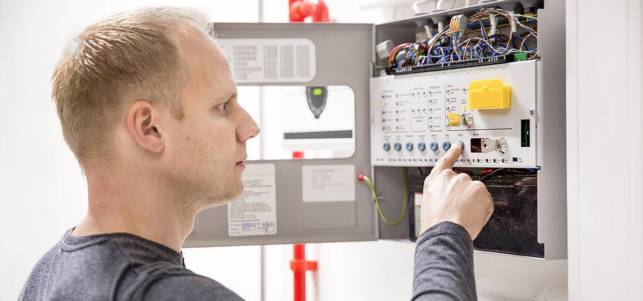 Technician checks fire panel in data cen