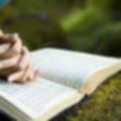 manos cruzadas de una mujer sobre una biblia abierta