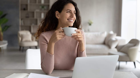 Smiling millennial Latino woman sit at desk at home office work online on computer drink c