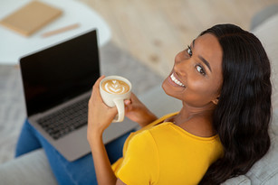 woman drinking coffee with computer on sofa