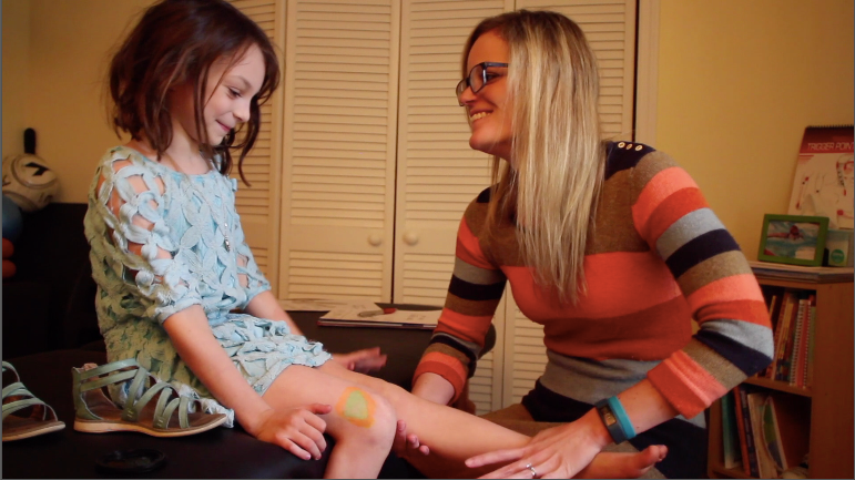 Julie smiling at one of her young female athlete PT patients