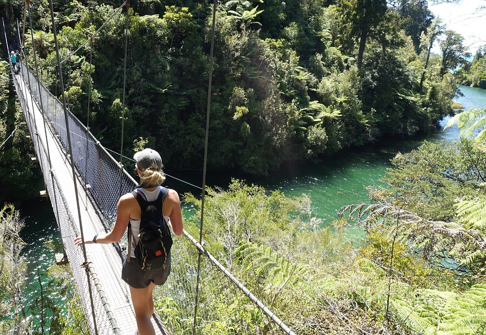 Julie crossing a suspension bridge while hiking in New Zealand