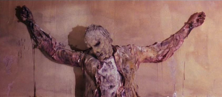 the corpse of the artist Sweick crucified to the wall