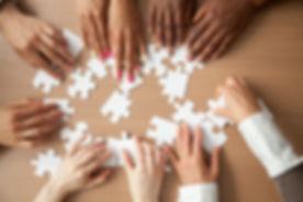Hands of diverse people assembling jigsa