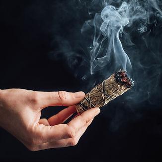burning-sage-smudge-stick-on-black-backg