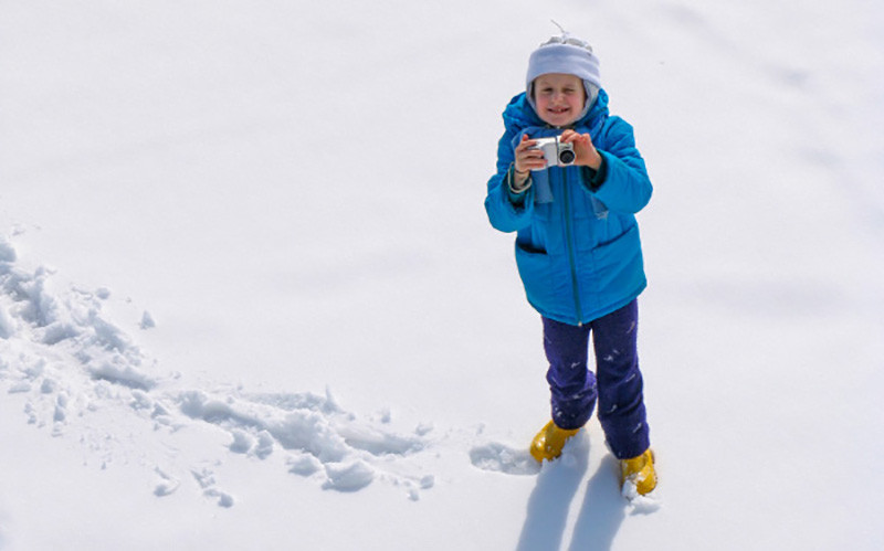 Child in snow with camera