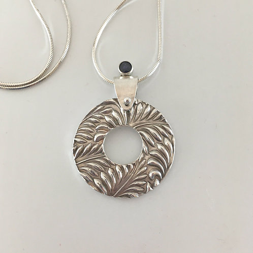 Patterned Round Pendant with a Tube Set Iolite Stone