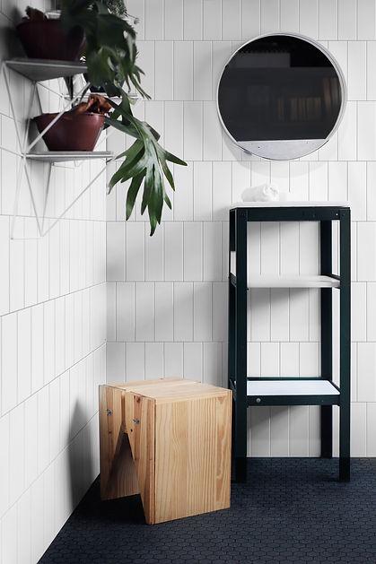 Decoração de banheiro com espelho redondo e suporte modular para plantas