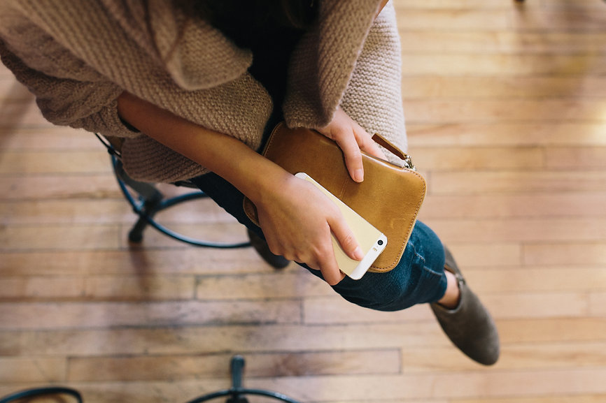 Woman business owner holding iPhone & leather notebook