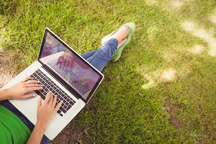 Woman business owner typing on her laptop outdoors