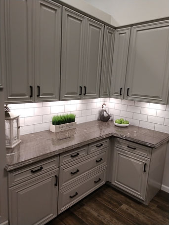 Grey kitchen cabinets with granite countertops and a white subway tile backsplash.