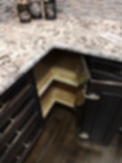 Kitchen cabint with wood lazy susan and granite countertop