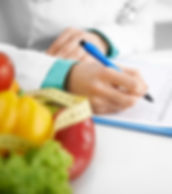 nutritionist writing on pad for the nutritionist sevices button below