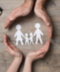 a paper cut out of a family wih two peoples hands as if supporting the family