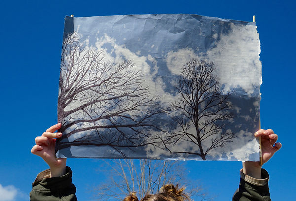 The same image is on the sheet as it is being held up by a person who is looking up with a mask on. The paper is held up to a clear blue sky and a tree can be seen behind the person's head underneath the sheet of paper.