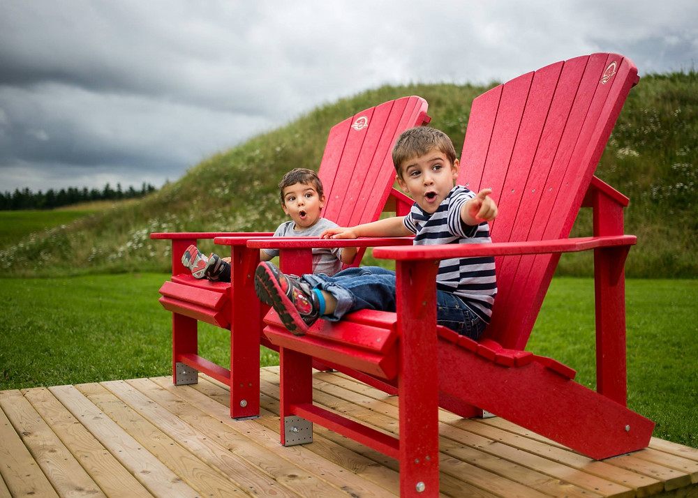 Kids sitting on chairs looking excited and pointing