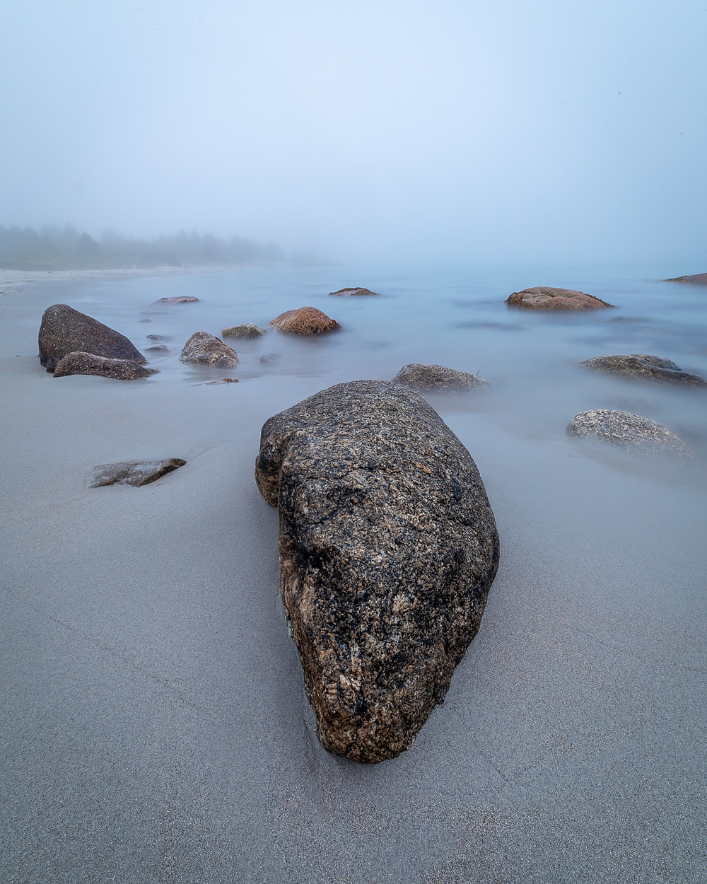 A rock in the foreground on a white sandy beach, with thick fog.