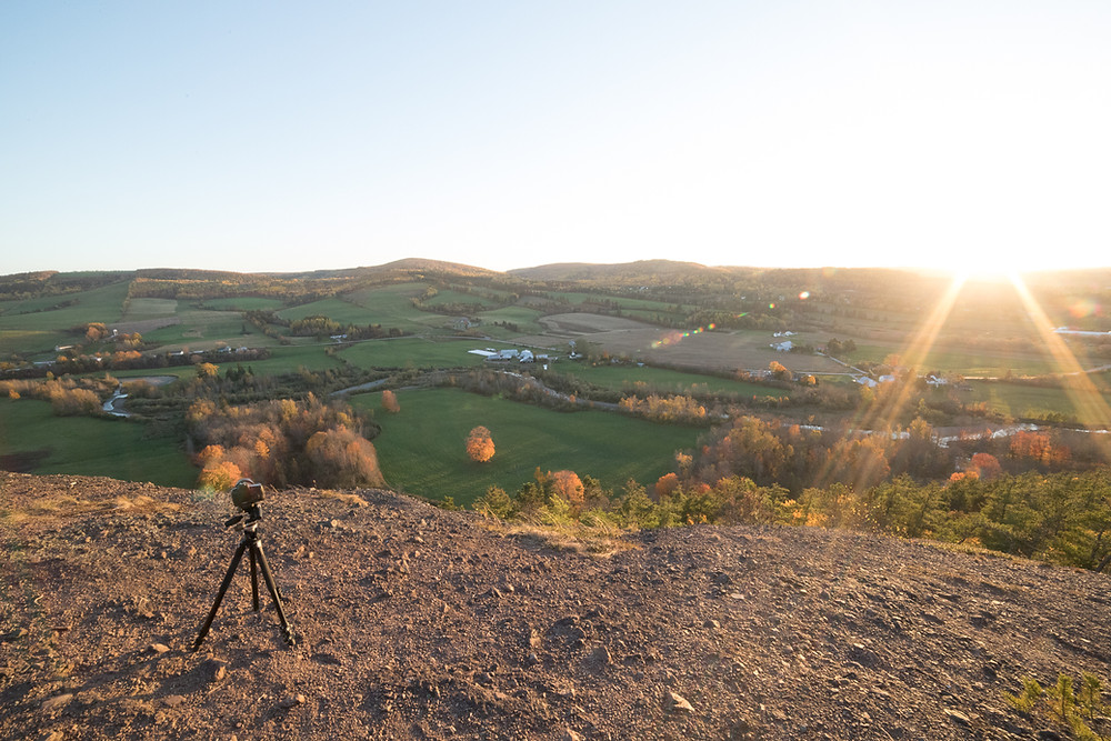 a camera on a tripod on the edge of a cliff, overlooking a valley with farms and greenery