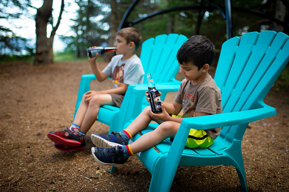 Kids sitting at a camp site and enjoying a beverage