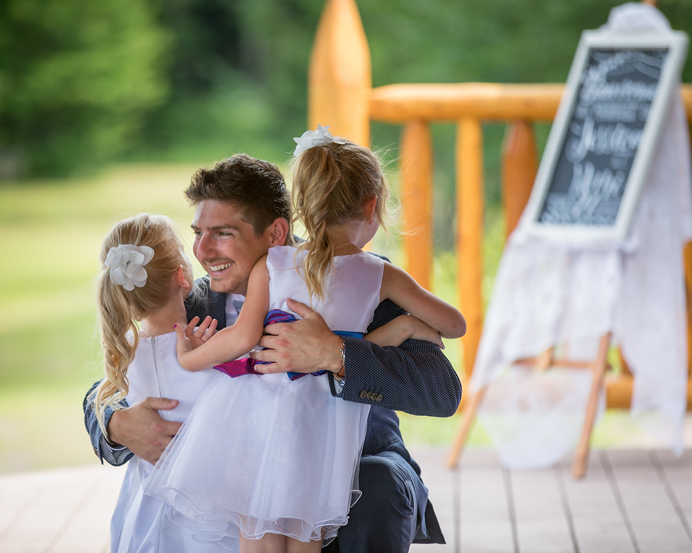 A groom hugs his two daughters at his wedding
