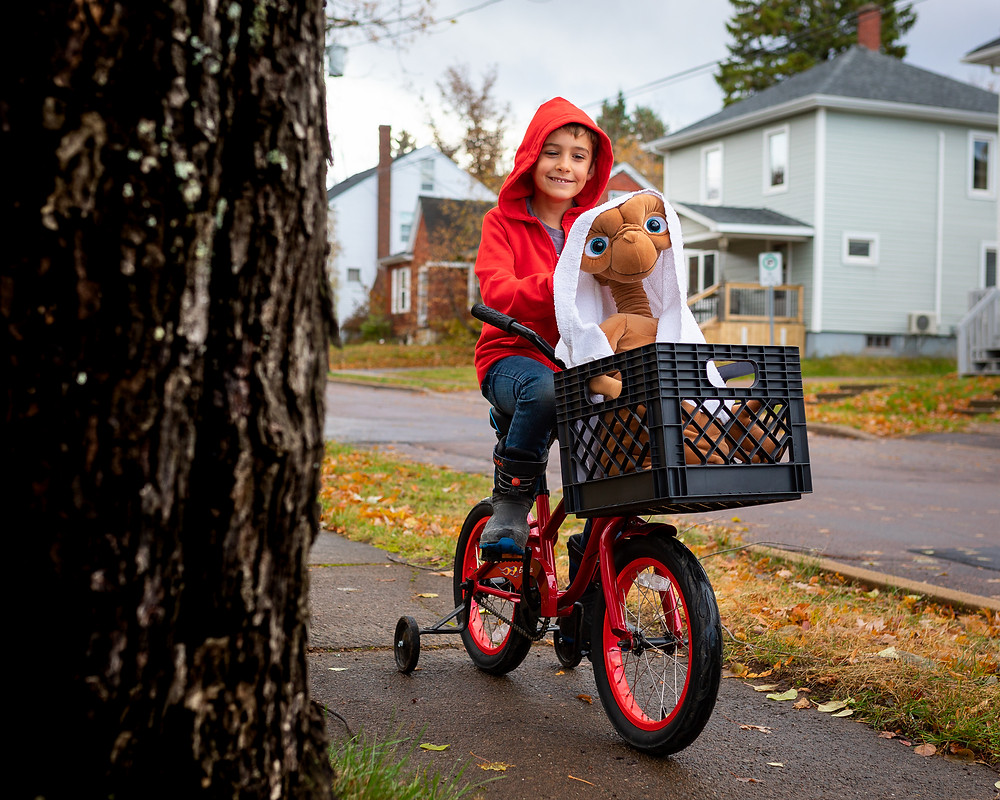 A kid on a bicycle with the E.T. character in front of it.