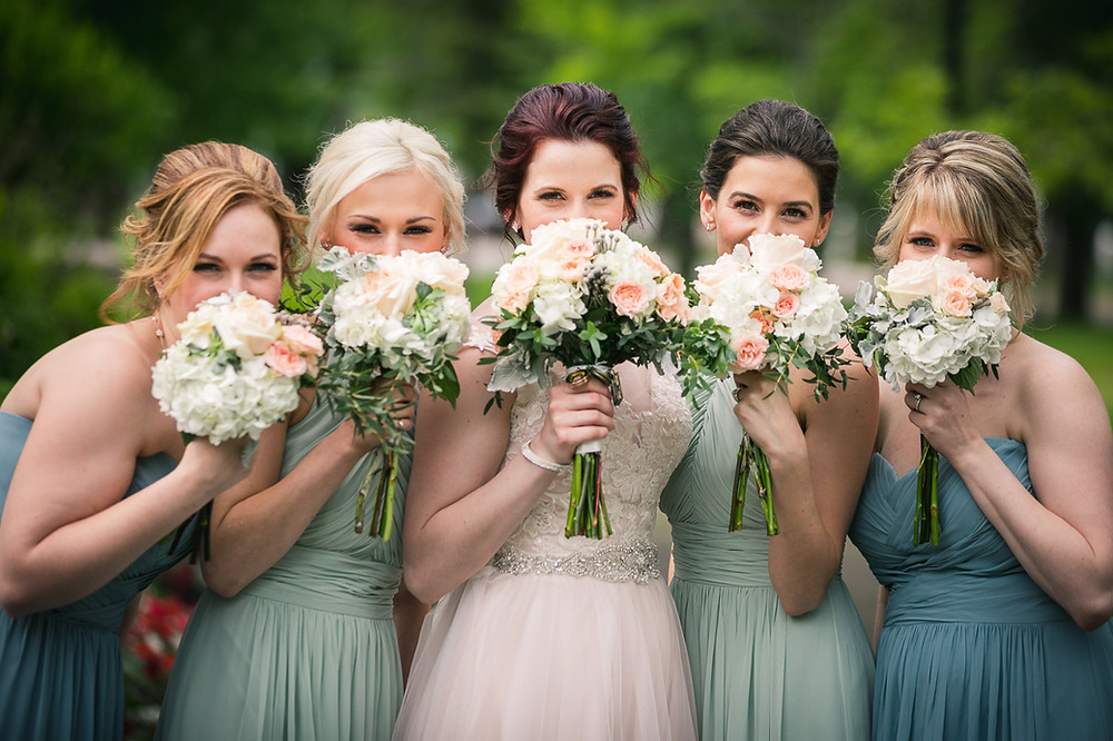 Bride and bridesmaids covering their faces with their bouquets