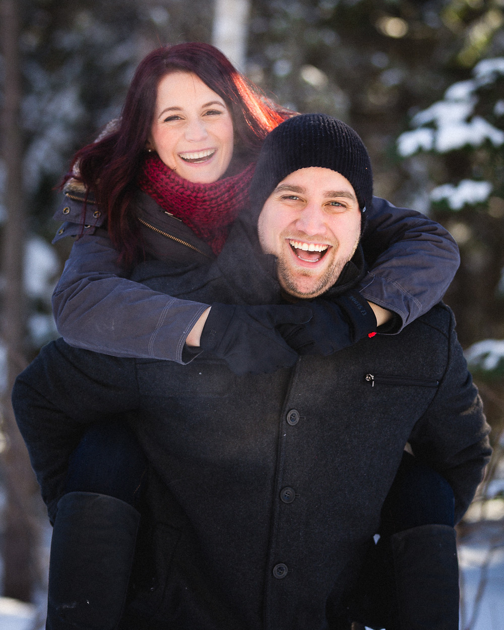 A happy couple in a wooded area, in winter.