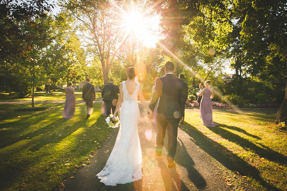 A couple walks towards the sun in a beautiful urban park