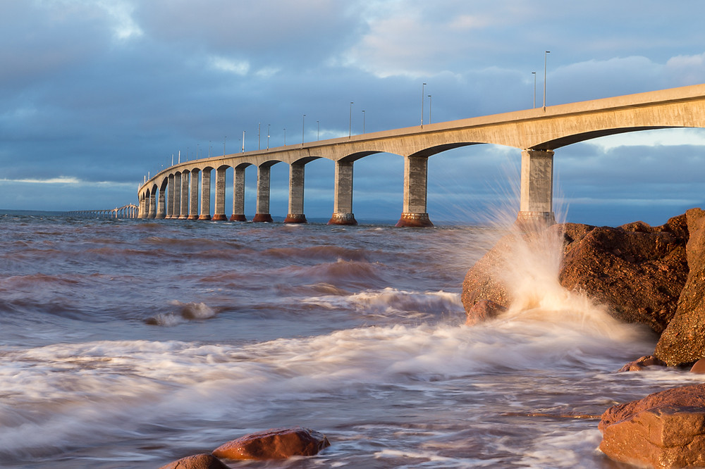 A wave crashes on the shore near the Confederation Bridge.