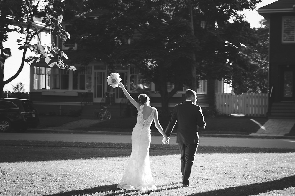 Bride and groom are walking away, bride has her bouquet up in the air