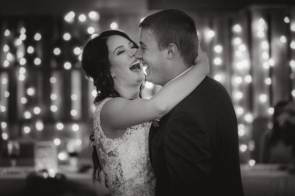 A couple laugh during their first dance at their wedding reception.
