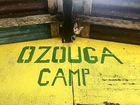 Der Ozouga Camp Schriftzug an einer der Hütten. Auch unsere Camp-Katze Lily hat hier ein schattiges Plätzchen.