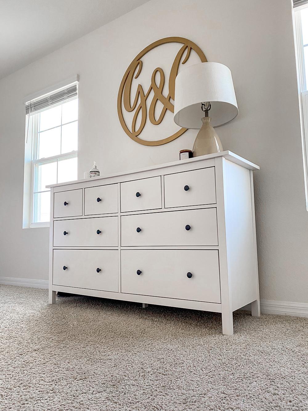 minimalist white drawer and signature monogram wall art