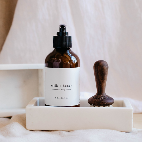 White marble soap tray holding lotion bottle and walnut shaving brush. Sold by Salt creek mercantile.