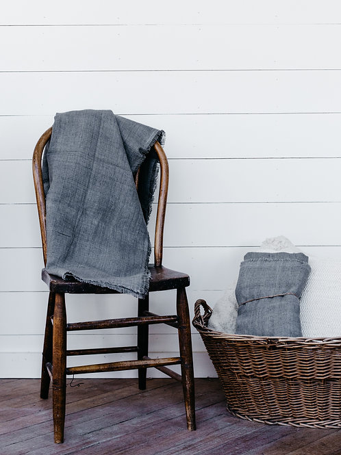 100% Linen Throw draped over farmhouse wooden chair. Sold by Salt Creek Mercantile.