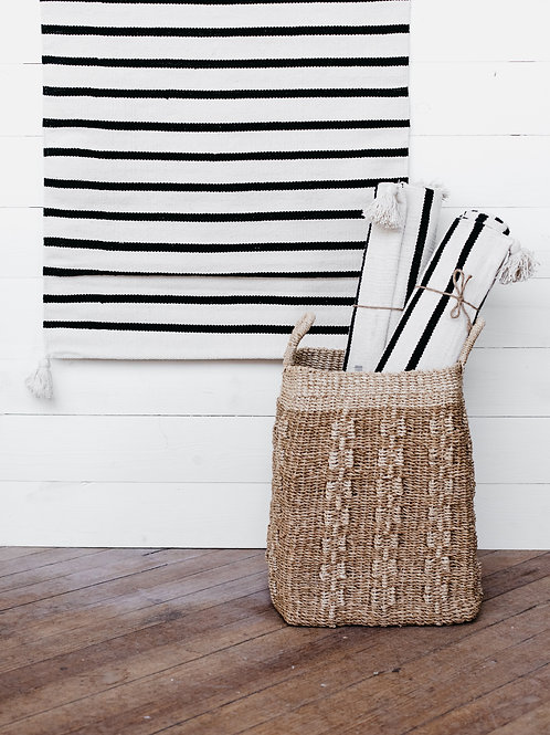 Striped floor runner displayed in a wicker basket and on a farmhouse shiplap wall. Sold by Salt Creek Mercantile.