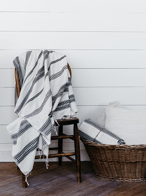 Lightweight and soft throw blanket, displayed on farmhouse wooden chair. Sold by Salt Creek Mercantile.