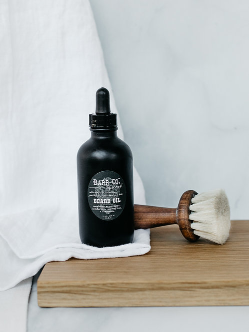 Beard oil in a black jar with dropper, displayed with walnut shaving brush. Sold by Salt Creek Mercantile.
