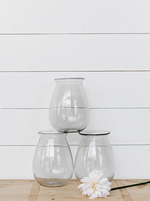 Clear Elodie Glass Vase, displayed in front of farmhouse shiplap wall. Sold by Salt Creek Mercantile.