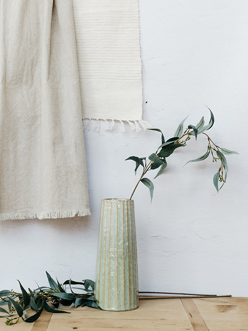 Artificial seeded eucalyptus branch displayed in the green, Palm vase. Sold by Salt Creek Mercantile.