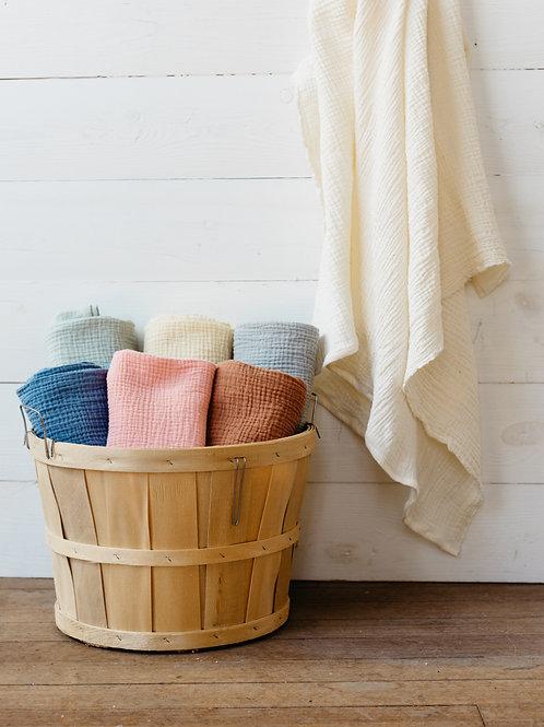 Basket of local handmade cotton gauze swaddles sold by Salt Creek Mercantile.