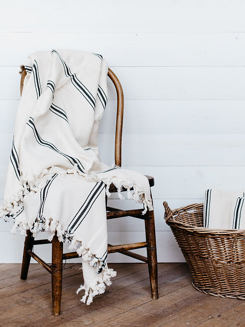 Striped, Turkish cotton throw draped over a farmhouse chair. Sold by Salt Creek Mercantile.