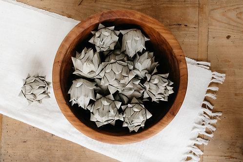 Muted green artichoke vase filler in wooden bowl. Sold by Salt Creek Mercantile.
