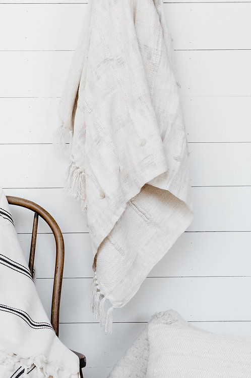 Textured throw blanket hanging on a farmhouse shiplap wall. Sold by Salt Creek Mercantile.