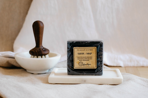 Lotantique black bar soap, sitting on a white marble soap tray. Sold by Salt Creek Mercantile.