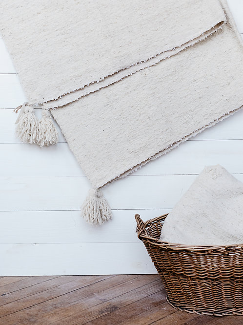 Beautifully textured, handwoven throw blanket displayed on a farmhouse shiplap wall. Sold by Salt Creek Mercantile.