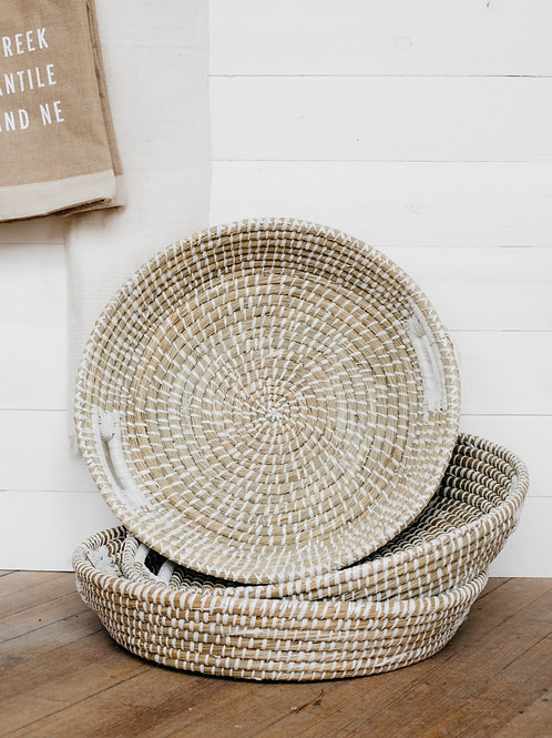 3 handwoven grass baskets stacked in front of white shiplap. Sold by Salt Creek Mercantile.