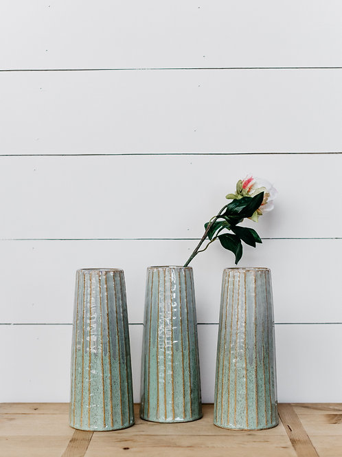 Green ceramic vases, displayed with silk florals in front of farmhouse shiplap at Salt Creek Mercantile.