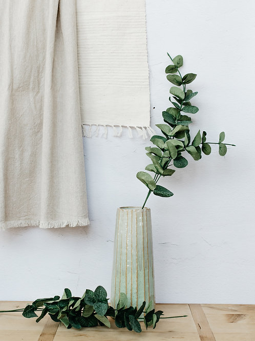 Artificial eucalyptus spray displayed in green Palm vase. Sold by Salt Creek Mercantile.